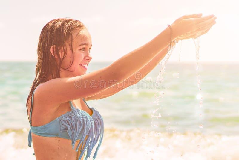 Mooie vrouw in bikini die bij de kust zonnebaden stock afbeeldingen