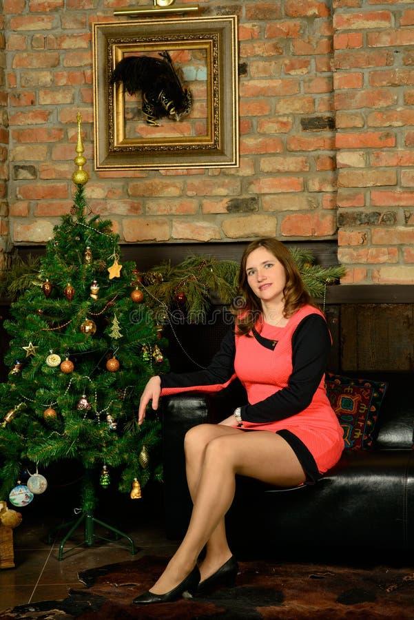Mooie vrouw in blauwe avondjurkzitting dichtbij Kerstboom royalty-vrije stock fotografie
