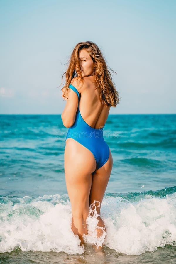 Mooie vrouw in blauwe bikini in oceaan en het bekijken camera stock fotografie
