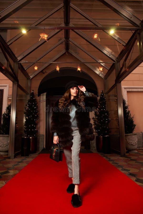 Mooie vrouw in bontjas het stellen op rood tapijt royalty-vrije stock afbeelding
