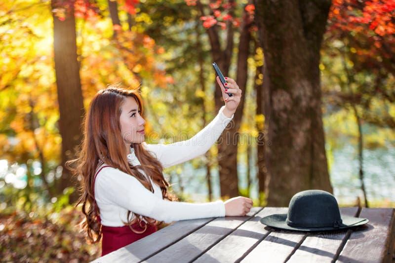 Mooie vrouw in dalings bospark die selfie zelffoto nemen stock fotografie