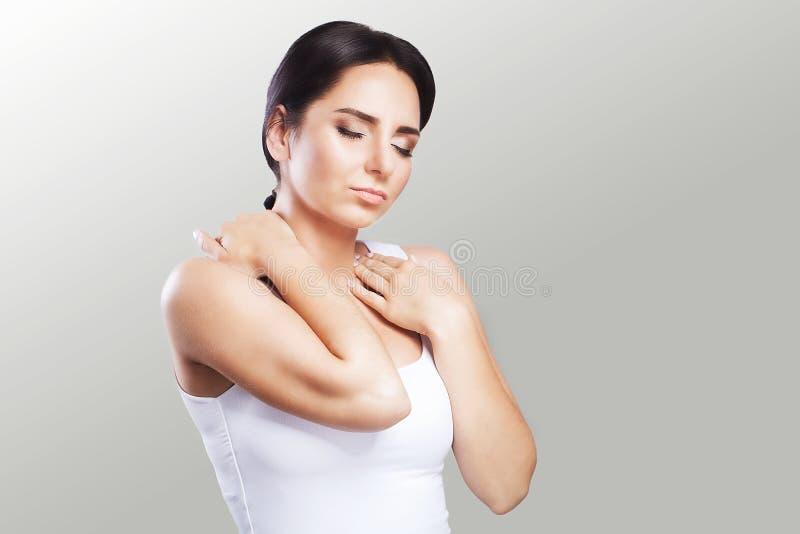 Mooie vrouw De vrouw houdt twee de hals en de schouders overhandigen dislocatie koude Spierspanning het concept gezondheid Op stock afbeeldingen