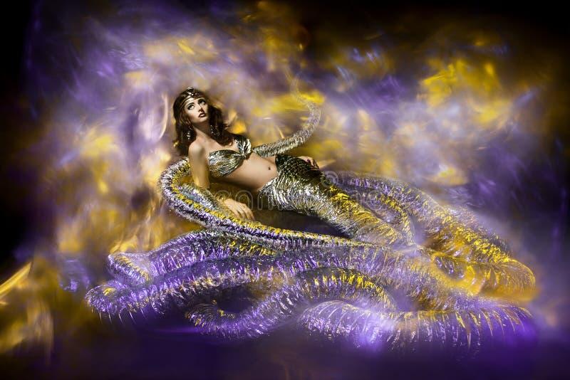 Mooie vrouw in de modieuze kleding van de fantasieslang. stock afbeeldingen
