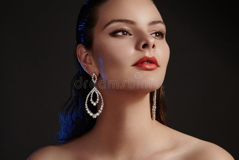 Mooie vrouw in de oorringen van de luxemanier Diamant glanzende juwelen met brilliants Toebehorenjuwelen, maniermake-up royalty-vrije stock foto's
