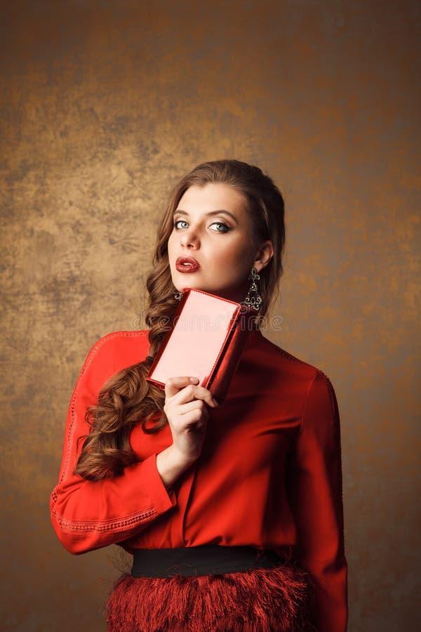 mooie vrouw in de rode beurs van de kledingsholding stock foto's