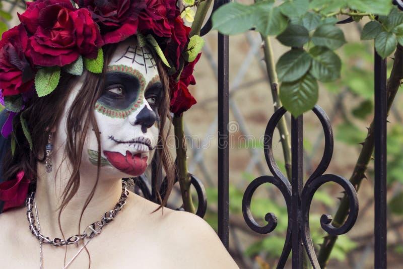 Mooie vrouw in de suikerschedel van make-up traditionele Mexicaanse Calavera op de achtergrond van een ijzeromheining met aren Da royalty-vrije stock afbeelding