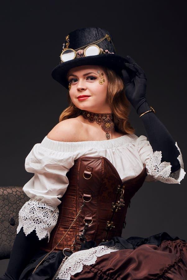 Mooie vrouw in de zitting van de steampunkstijl op de stoel stock foto