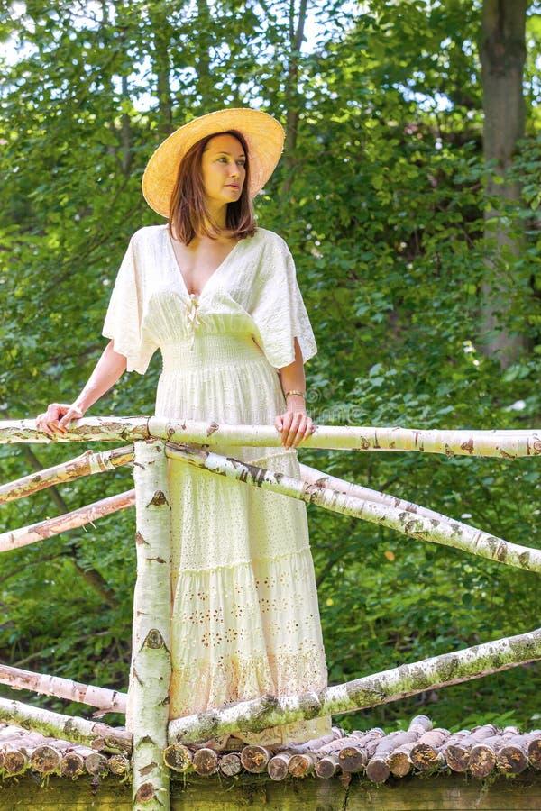 Mooie vrouw in de zomerhoed en witte kleding in een oud park royalty-vrije stock fotografie