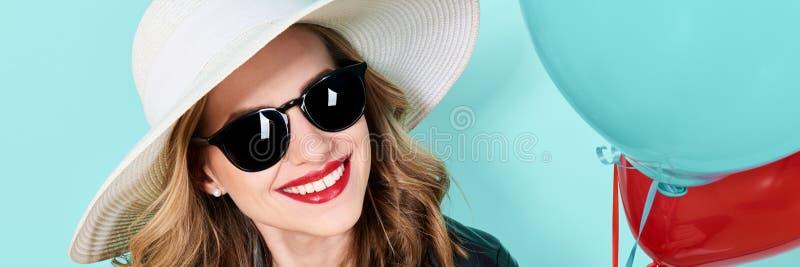 Mooie vrouw in de zomerhoed en zonnebril die ballons houden Het aantrekkelijke koele jonge portret van de vrouwenmanier stock foto