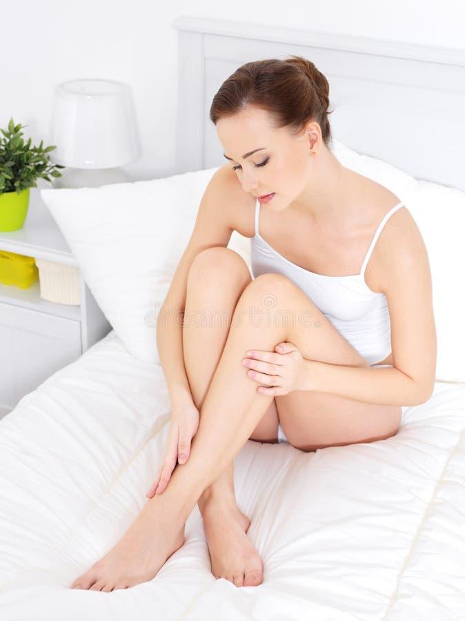 Mooie vrouw in dedroom wat betreft mooie benen royalty-vrije stock afbeeldingen