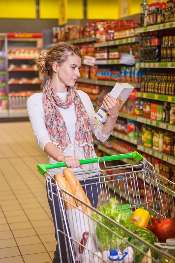Mooie vrouw die één of ander product in een supermarkt bekijken stock afbeelding