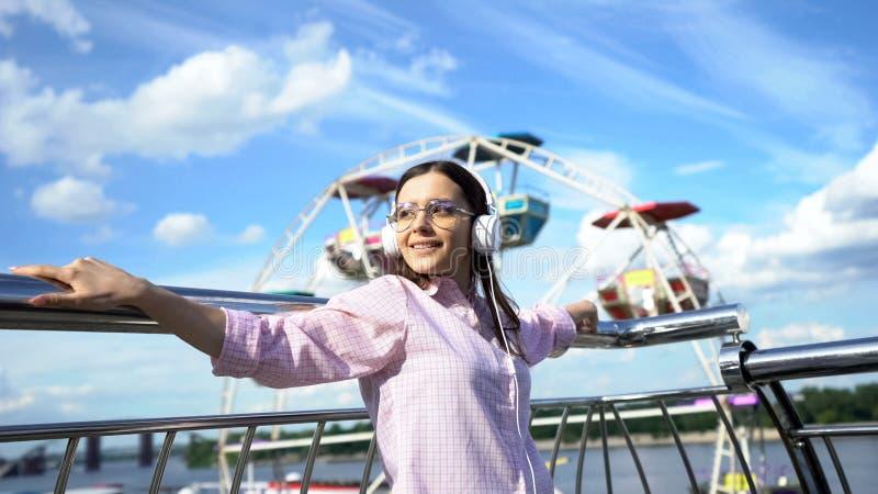 Mooie vrouw die aan het motiveren audiobook in hoofdtelefoons, inspiratie luisteren stock foto