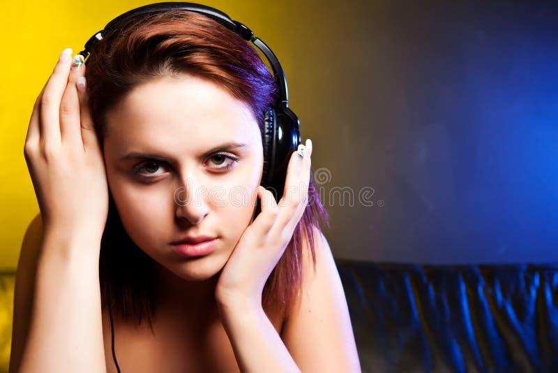 Mooie vrouw die aan muziek luistert stock foto's