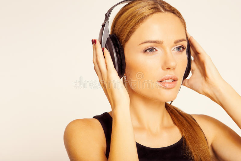 Mooie vrouw die aan muziek luistert stock foto