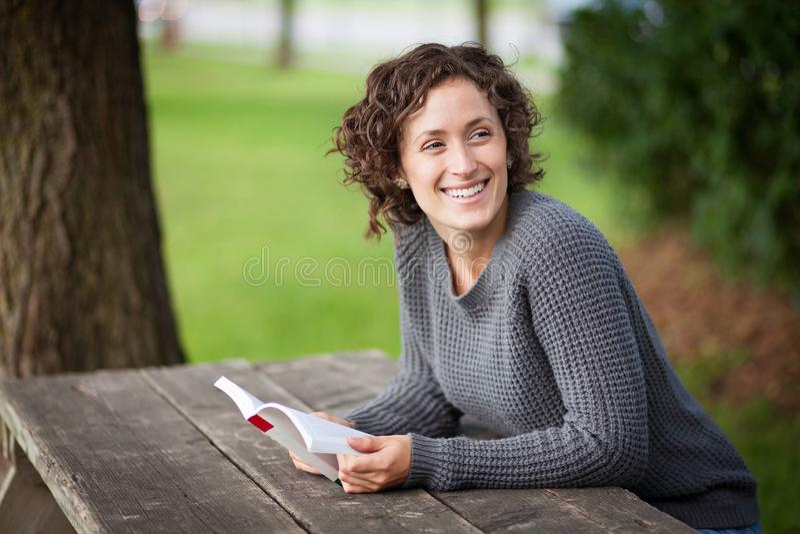Mooie vrouw die aan somebody achter haar glimlachen Zij is bij een picknicklijst royalty-vrije stock foto
