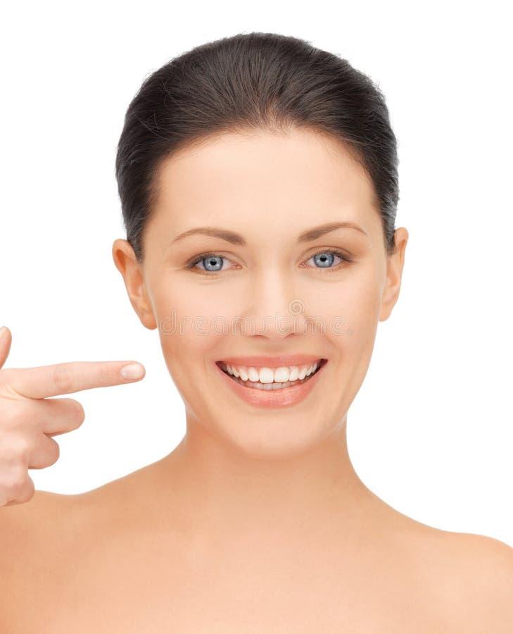 Mooie vrouw die aan tanden richt stock fotografie
