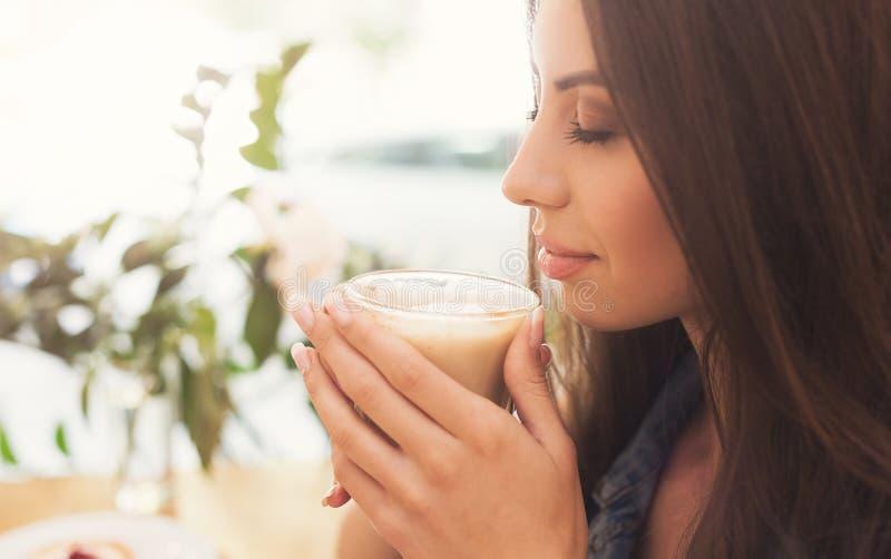 Mooie vrouw die aromatische koffie in de ochtend ruiken stock afbeeldingen