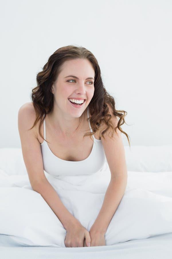Mooie vrouw die in bed glimlachen royalty-vrije stock afbeelding