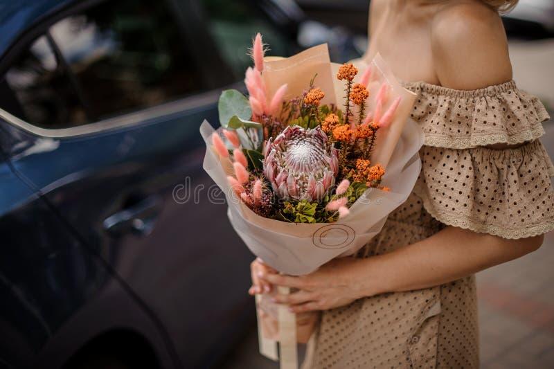 Mooie vrouw die in beige kleding met open schouders een nud houden stock fotografie