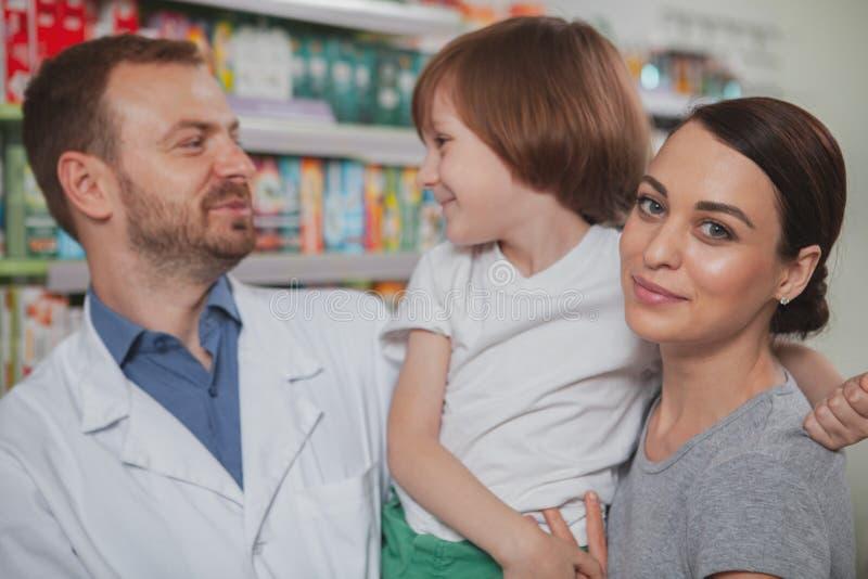 Mooie vrouw die bij drogisterij met haar winkelen weinig zoon stock fotografie