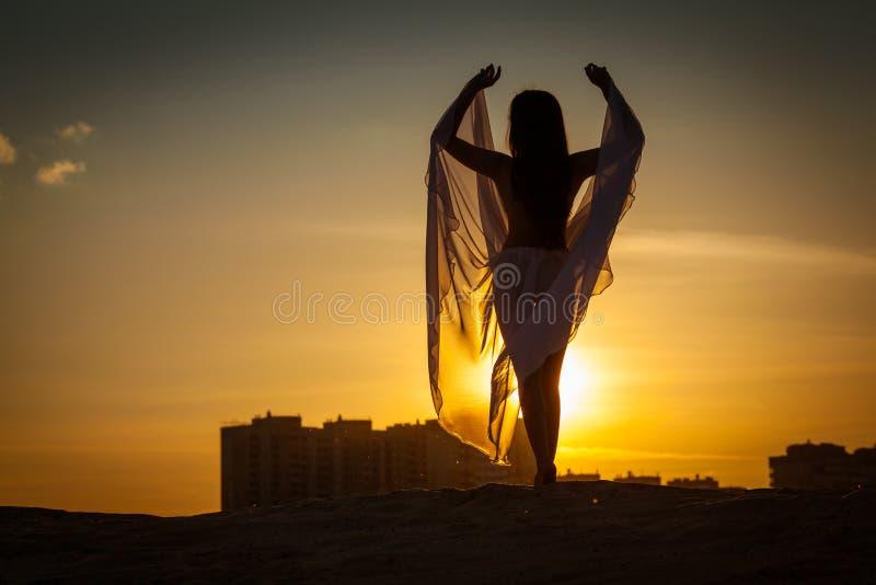 Mooie vrouw die bij zonsondergang dansen stock fotografie