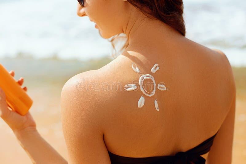 Mooie vrouw die in bikini zonroom op gelooide schouder toepassen Vrouw die zonneroom op schouder zetten dichtbij de pool Huid en  royalty-vrije stock afbeelding