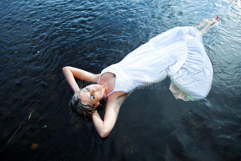 Mooie vrouw die in blauwe rivier drijft royalty-vrije stock foto's
