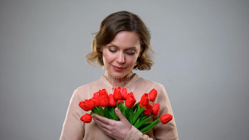 Mooie vrouw die bloemen van bewonderaar, romantisch heden, verjaardag bekijken stock afbeeldingen
