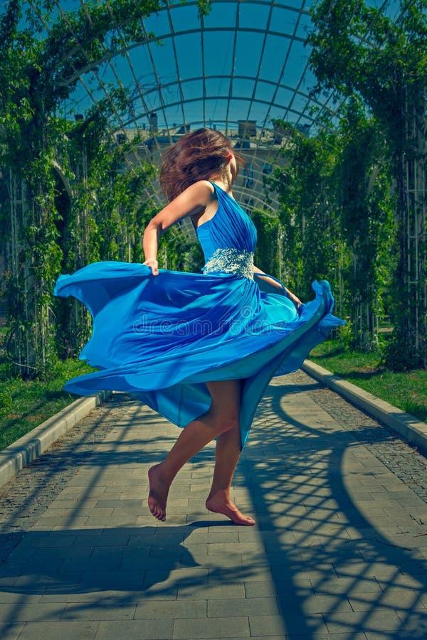 Mooie vrouw die blootvoets in een lange blauwe kleding dansen stock fotografie