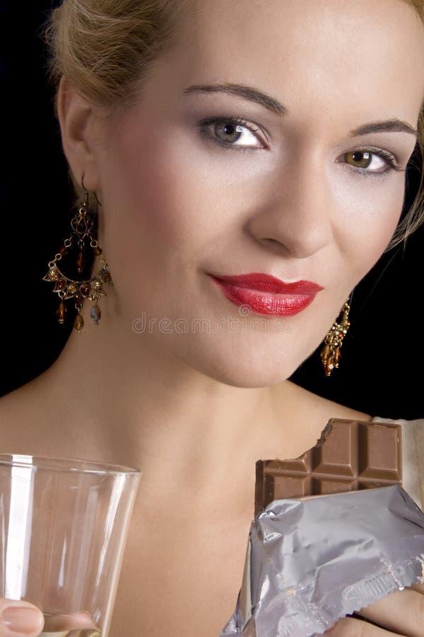 Mooie vrouw die chocolade eet stock afbeeldingen