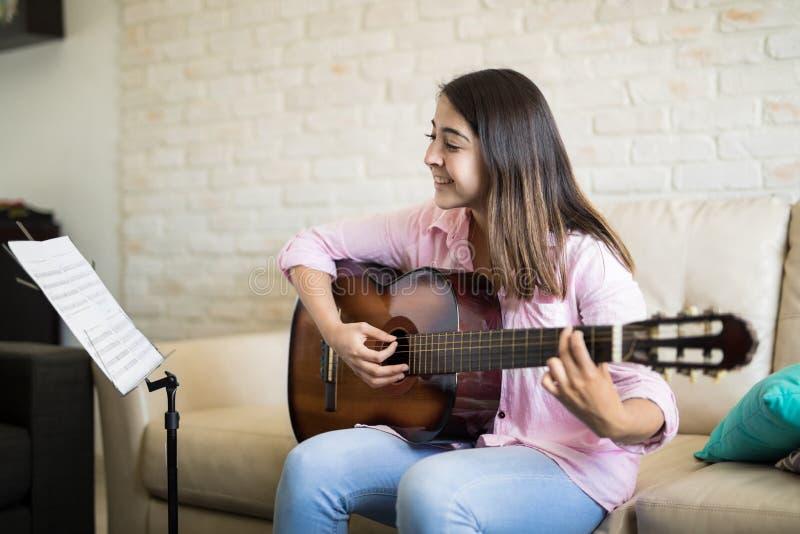 Mooie vrouw die de gitaar speelt stock foto's