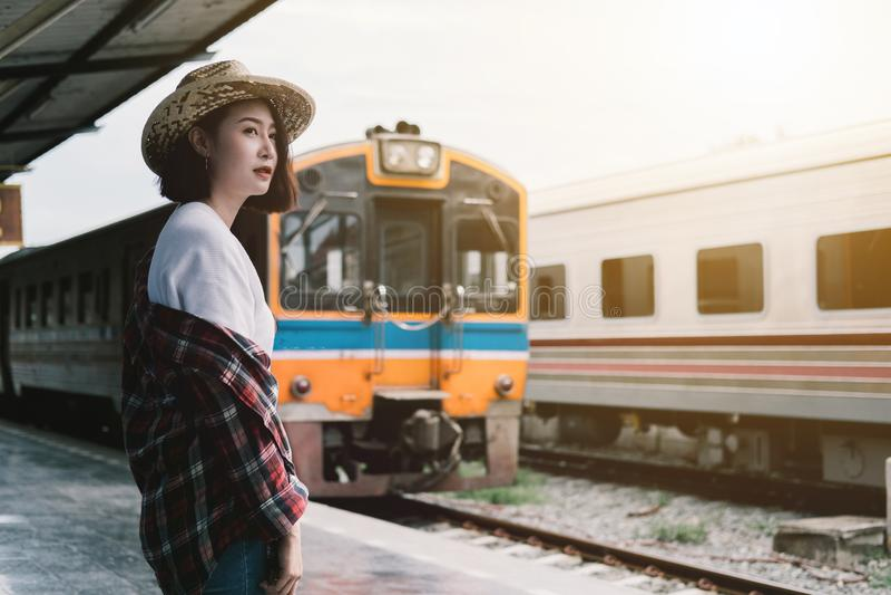 Mooie vrouw die de trein wachten bij station op reis in su stock afbeeldingen