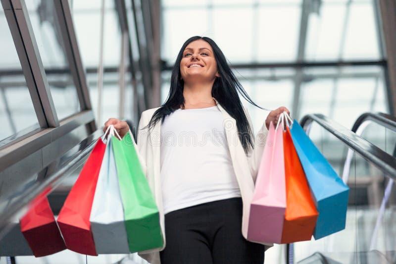 Mooie vrouw die de wandelgalerij met overvloed van het winkelen zakken verlaten royalty-vrije stock foto's