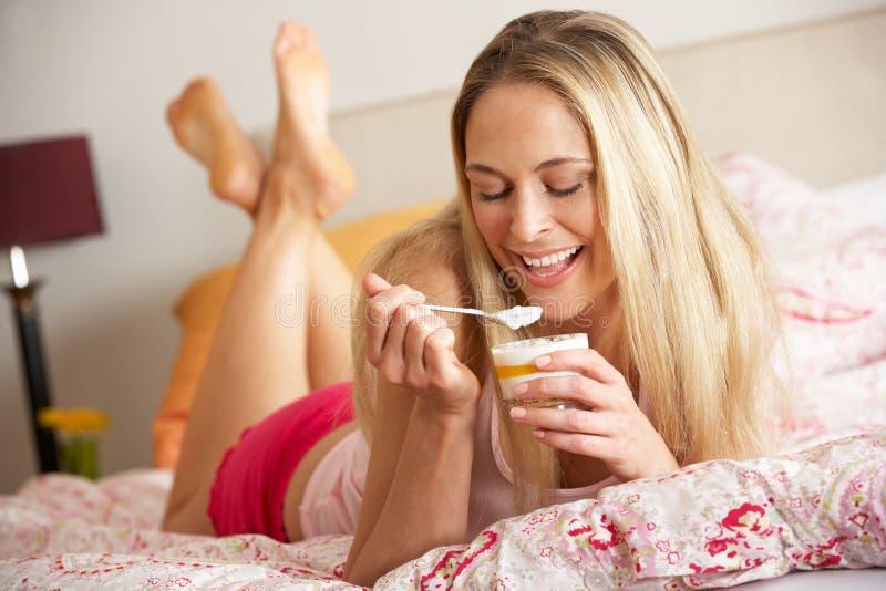 Mooie Vrouw die Dessert in Bed eet stock afbeeldingen