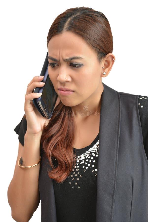 Mooie vrouw die door mobiele telefoon ongerust wordt gemaakt stock fotografie
