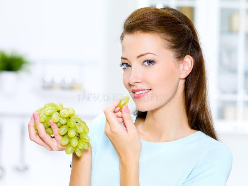 Mooie vrouw die druiven eet royalty-vrije stock afbeeldingen