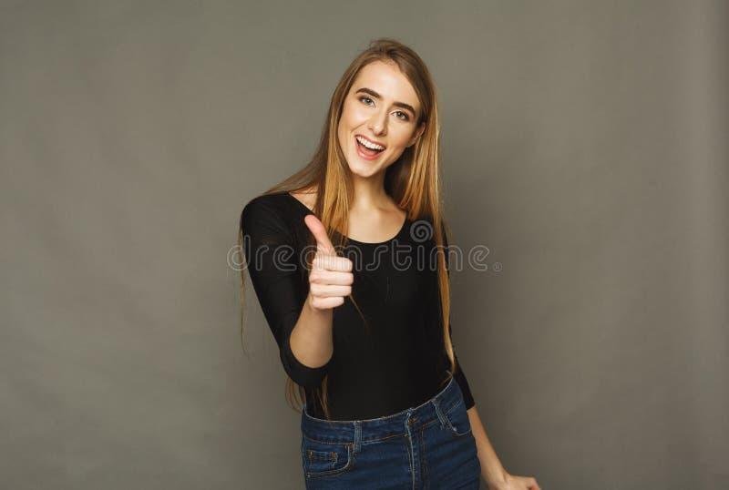 Mooie vrouw die duim in studio tonen stock fotografie