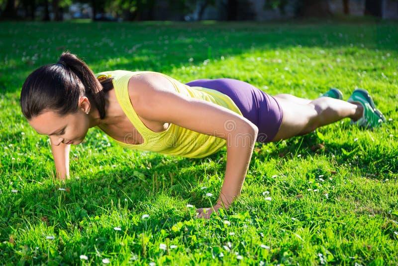 Mooie vrouw die duw op oefening in park doen stock afbeelding