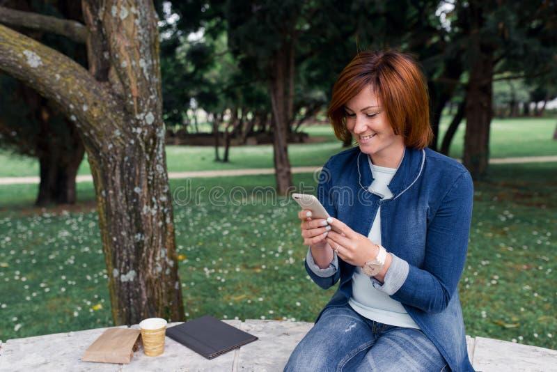 Mooie vrouw die een bericht op haar telefoon in het park verzenden royalty-vrije stock foto