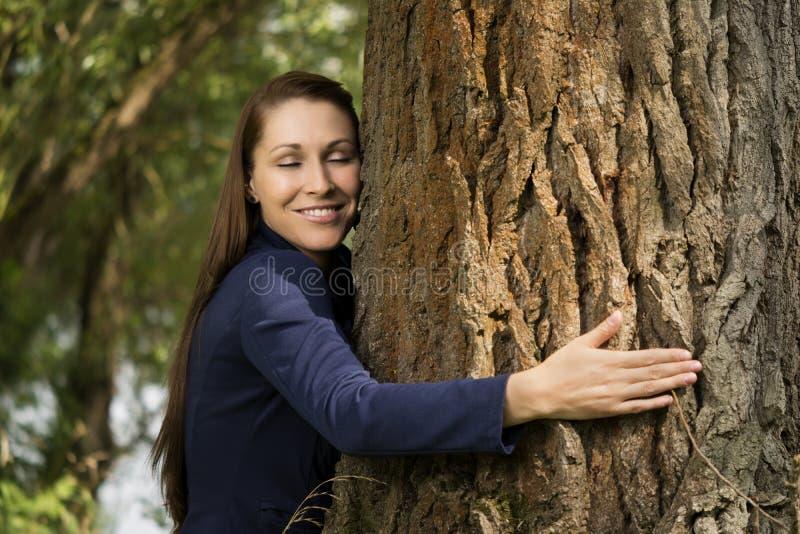 Mooie vrouw die een boom koesteren stock afbeelding