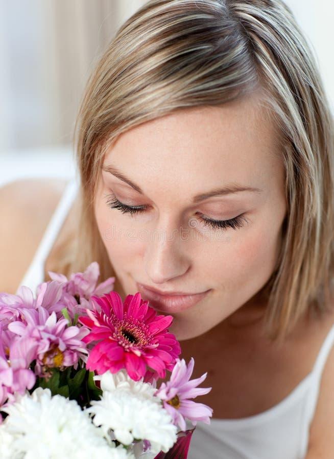 Mooie vrouw die een bos van bloemen ruikt royalty-vrije stock afbeeldingen