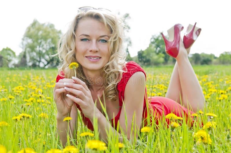 Mooie vrouw die in een boterbloemenweide liggen royalty-vrije stock foto