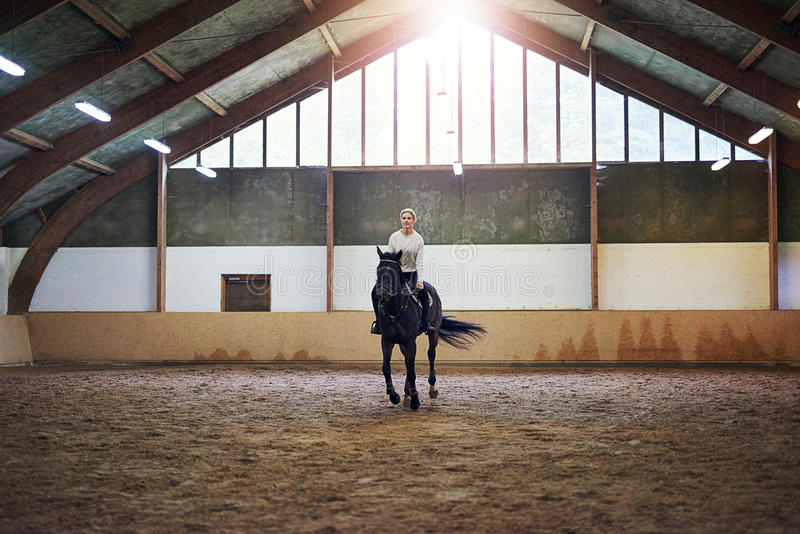 Mooie vrouw die een bruin paard berijden stock foto