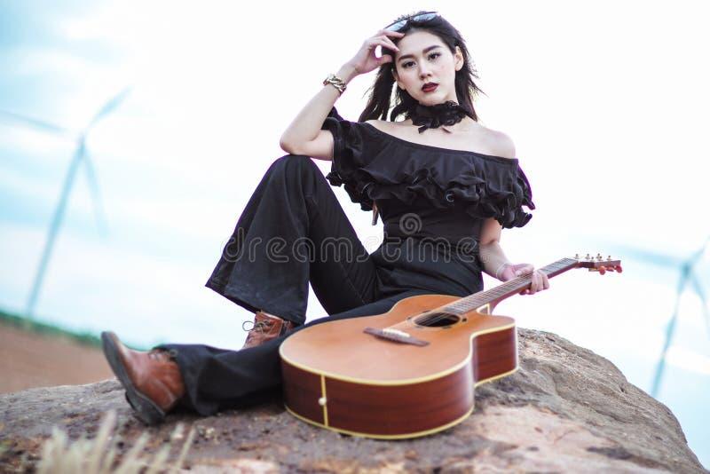 Mooie vrouw die een gitaar houden stock foto's