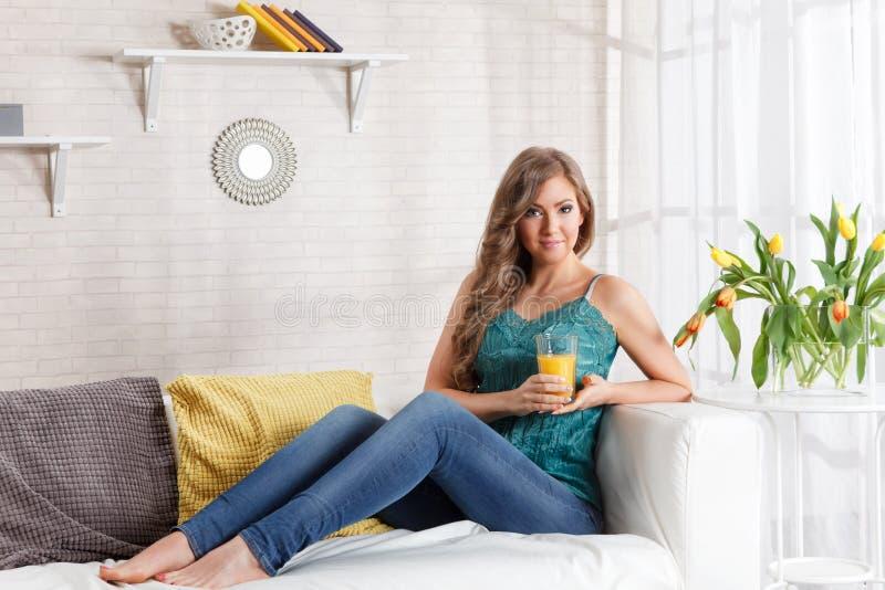 Mooie vrouw die een glas jus d'orange houden stock afbeeldingen