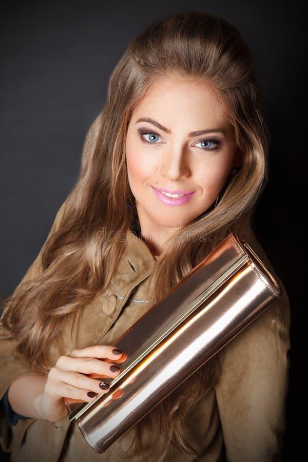 Mooie vrouw die een gouden koppeling houden stock foto's