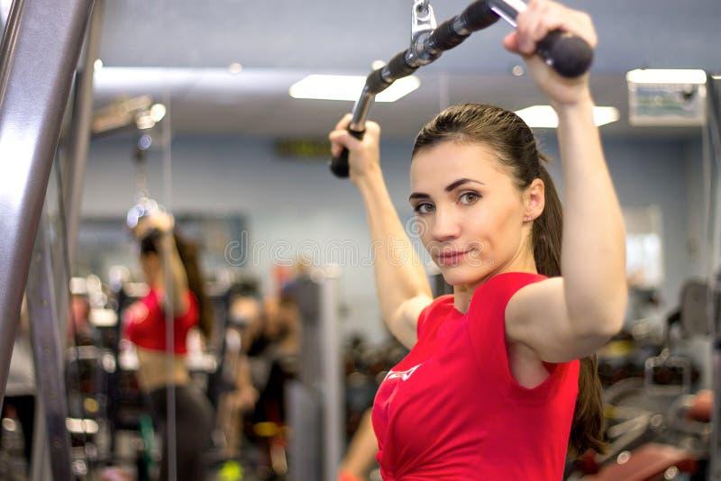 Mooie vrouw die in een gymnastiek uitwerken die onderzoekend ca glimlachen royalty-vrije stock afbeelding