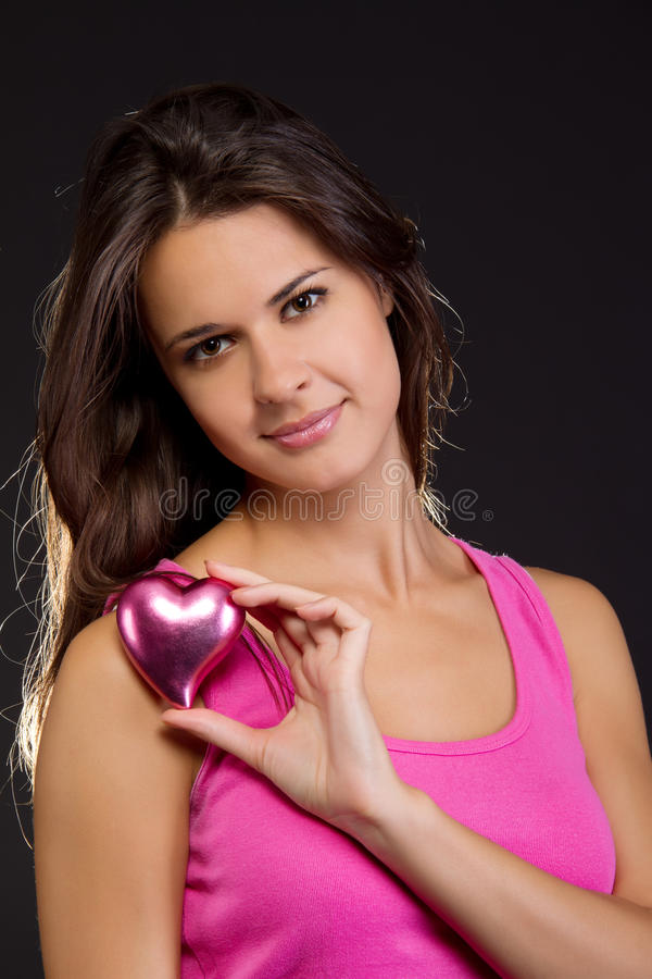 Mooie vrouw die een hart houdt stock foto