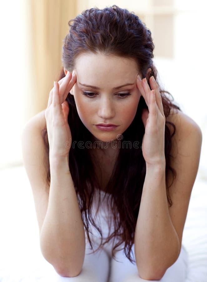 Mooie vrouw die een hoofdpijn in bed heeft royalty-vrije stock foto's