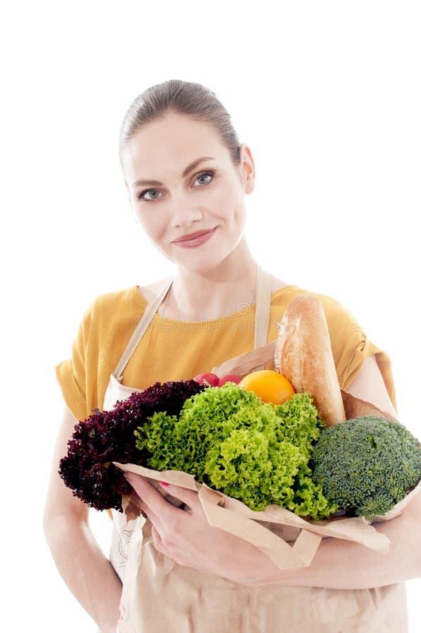 Mooie vrouw die een hoogtepunt van de kruidenierswinkelzak van groenten houden stock afbeelding
